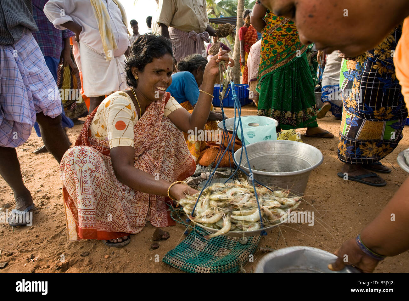 Tsunami survivors at Thalanguda fishing community the wife of a fisherman weighs fresh prawns to sell. - Stock Image