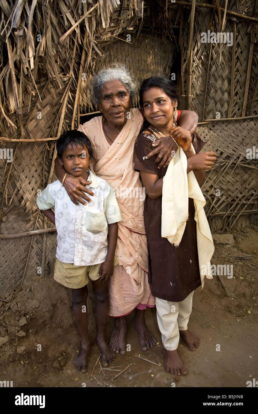 Tsunami survivors a granny and her grandchildren outside her bamboo shack Uppulavadi India - Stock Image