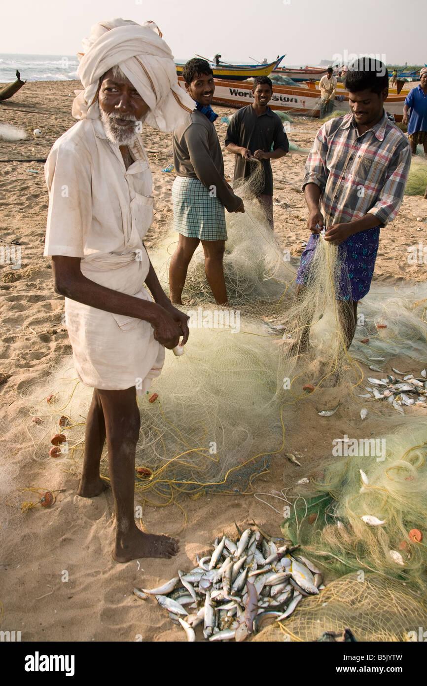 Tsunami survivors fishermen unload their nets of fish on Thalanguda beach Tamil Nadu - Stock Image