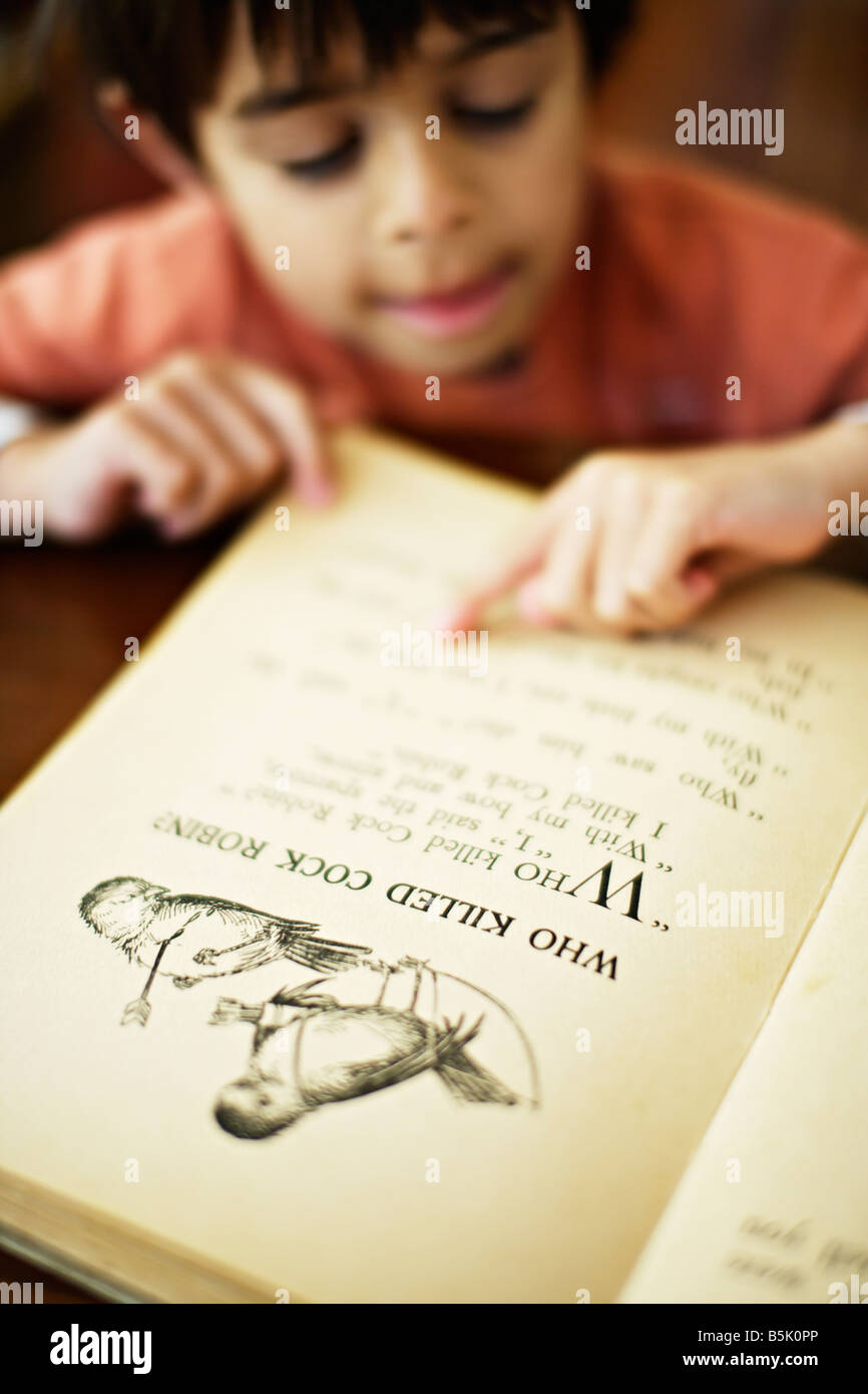 Six year old boy points to words in book as he learns to read - Stock Image