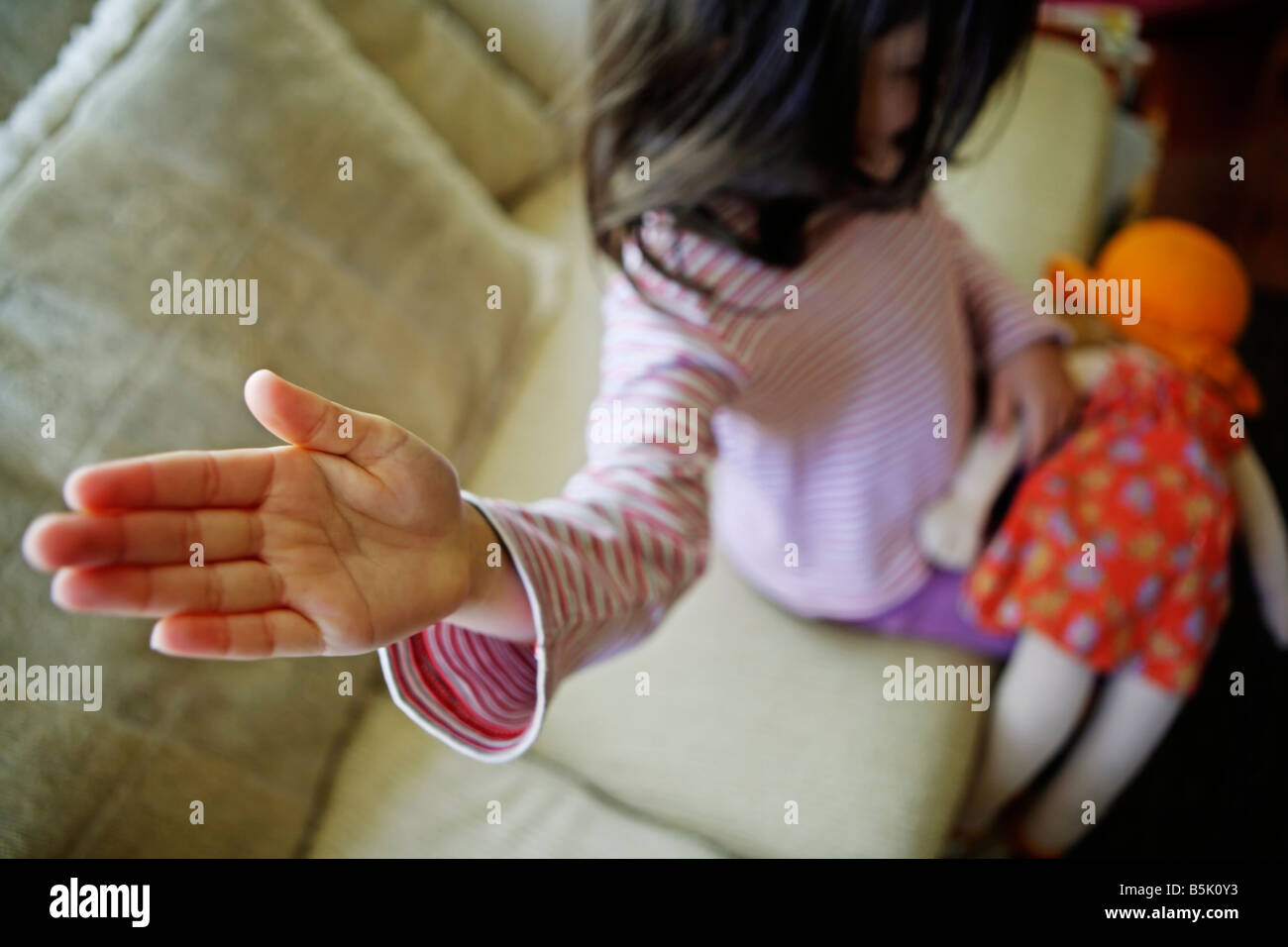 Five year old girl smacks doll Stock Photo