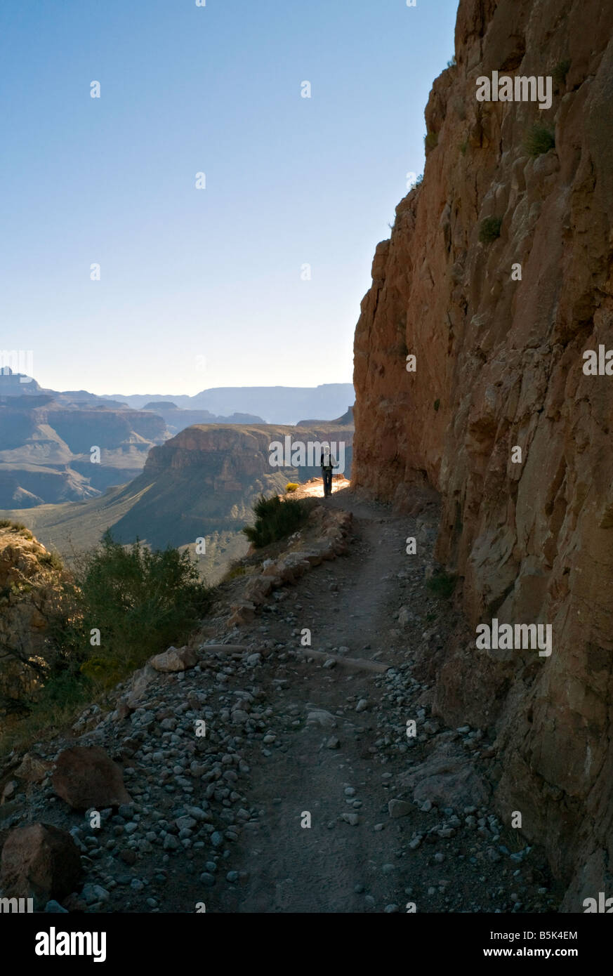 ARIZONA GRAND CANYON Hiker stops to admire the view at sunrise as she hikes down the South Kaibab Trail into the - Stock Image