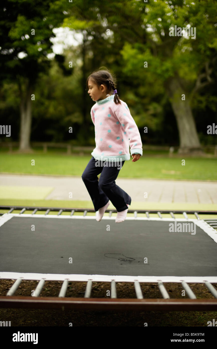 Five year old girl bouncing on a trampoline - Stock Image