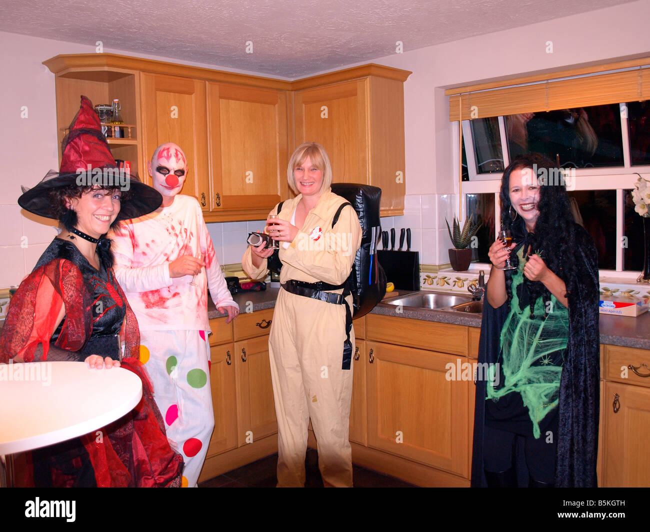A Halloween party with fancy dress witches,ghost buster,and mad clown. - Stock Image