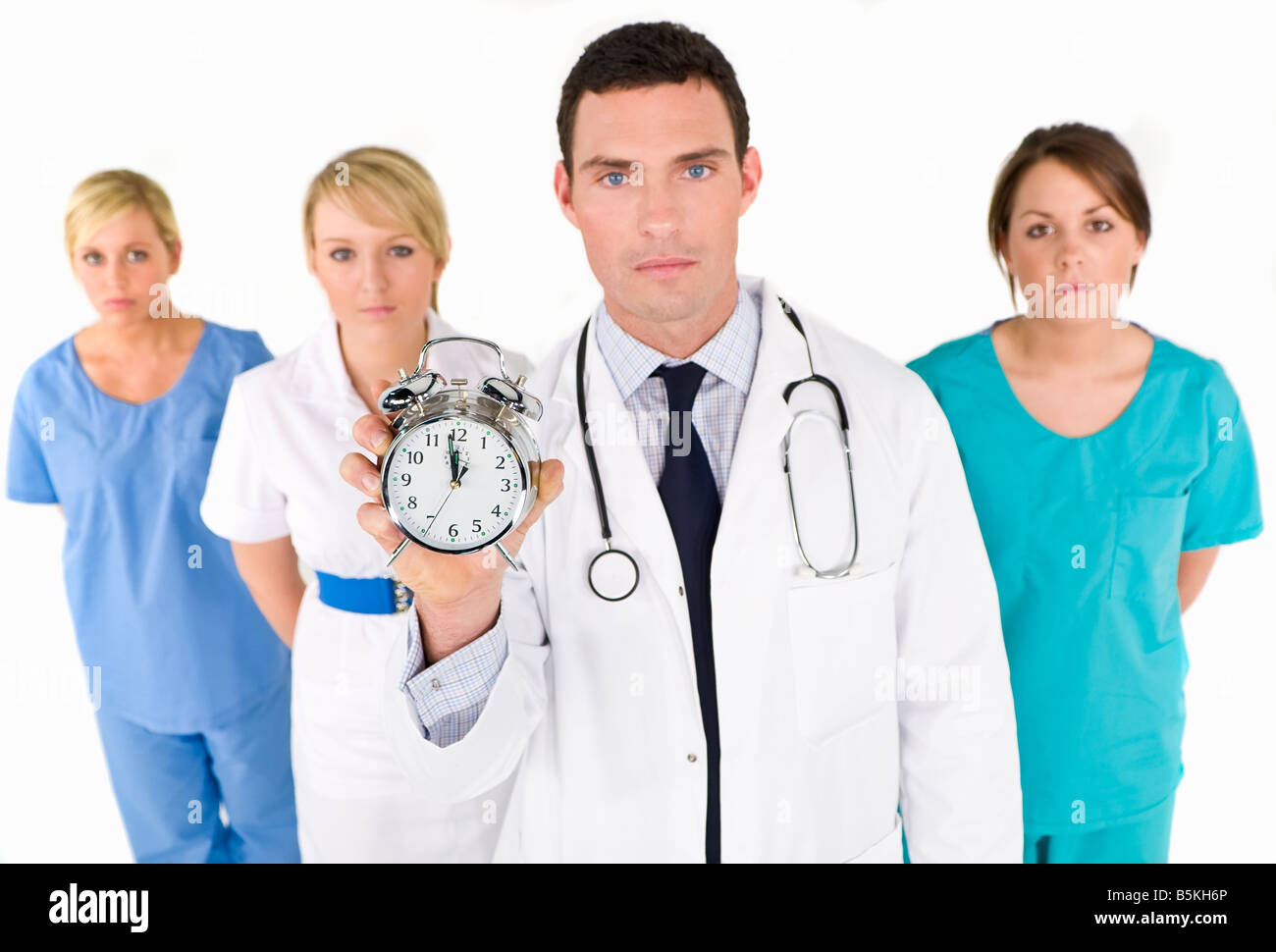 A male doctor backed by his medical team holding out an alarm clock ticking ever closer to 12 o clock. Focus on - Stock Image