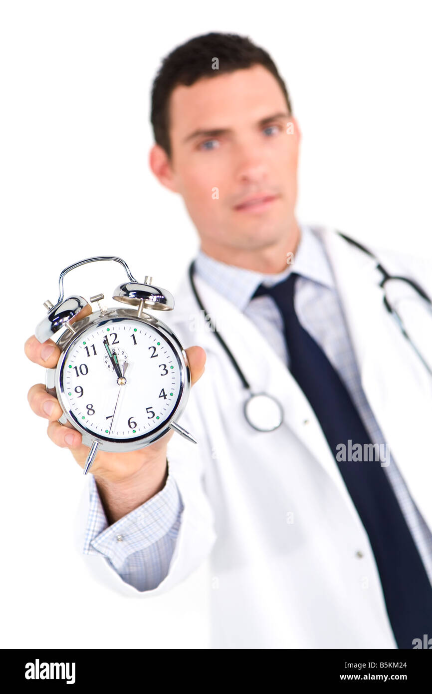 A male doctor holding out an alarm clock ticking ever closer to 12 o clock The focus is on the clock face - Stock Image