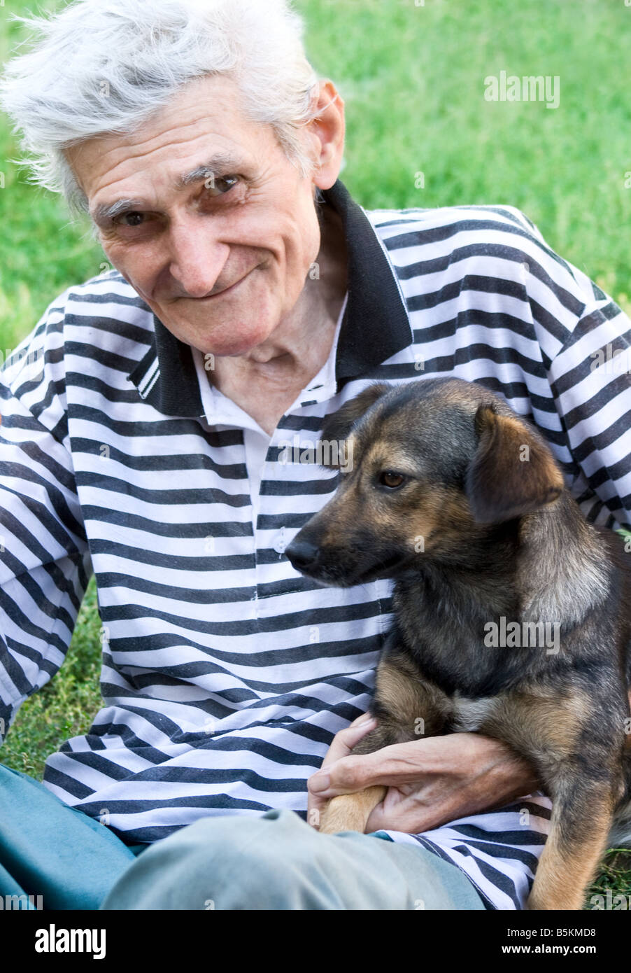 Portrait of happy male senior with his best pal a cute dog - Stock Image