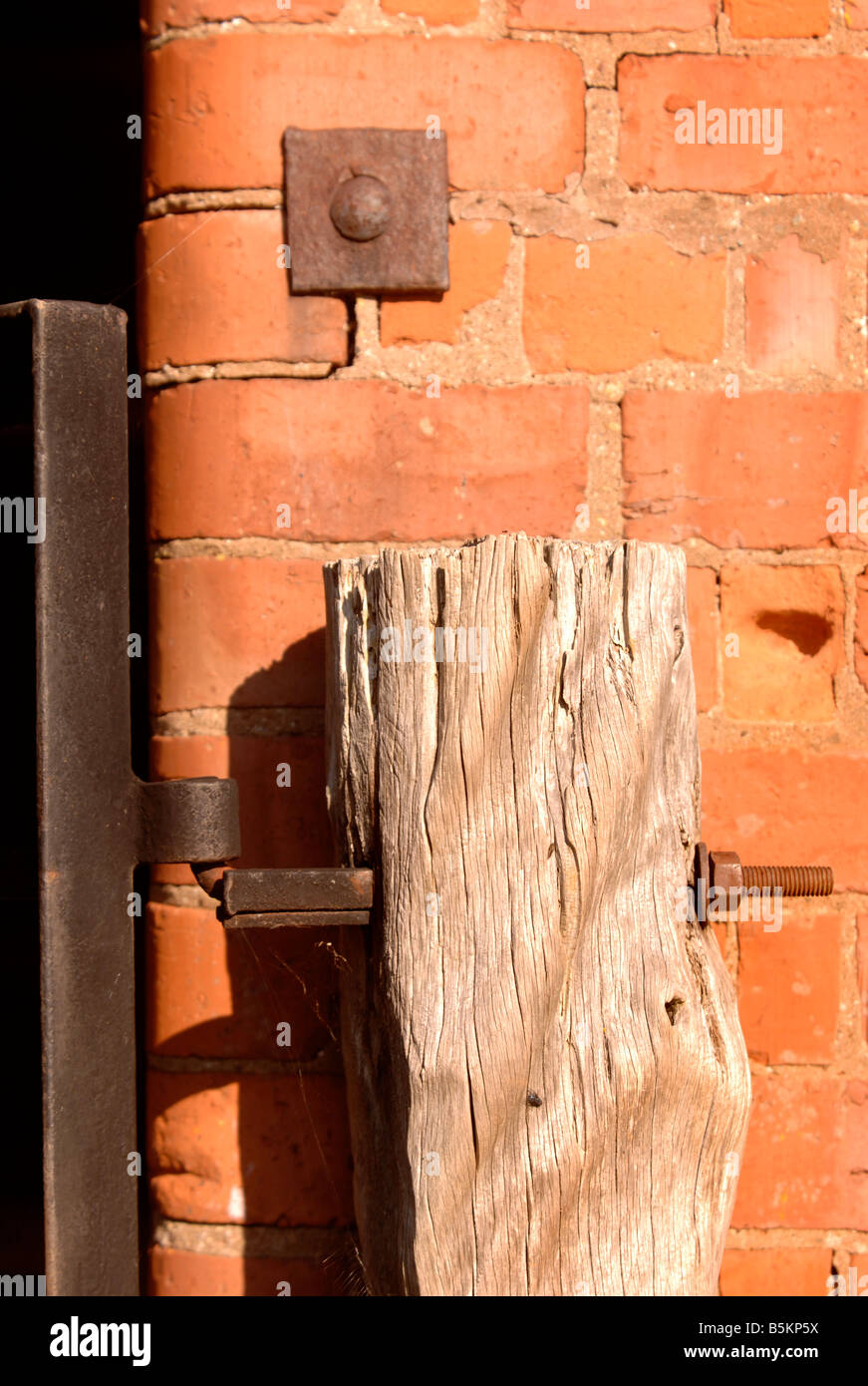 DETAIL OF A RED BRICK BARN WITH RUSTIC TIMBER GATEPOST IN HEREFORDSHIRE UK - Stock Image