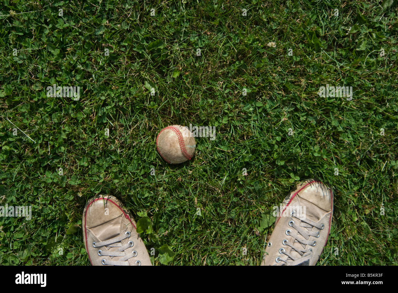 Close up of a man s feet next to a baseball MODEL RELEASED - Stock Image