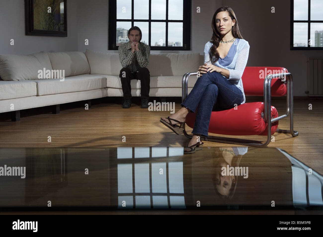 Young man and woman with computer in a living room Stock Photo
