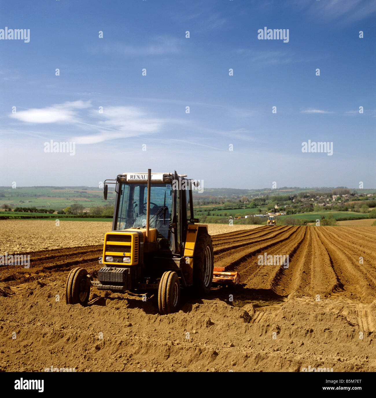 UK England Gloucestershire agriculture Renault tractor preparing field for planting in West Cotswolds - Stock Image