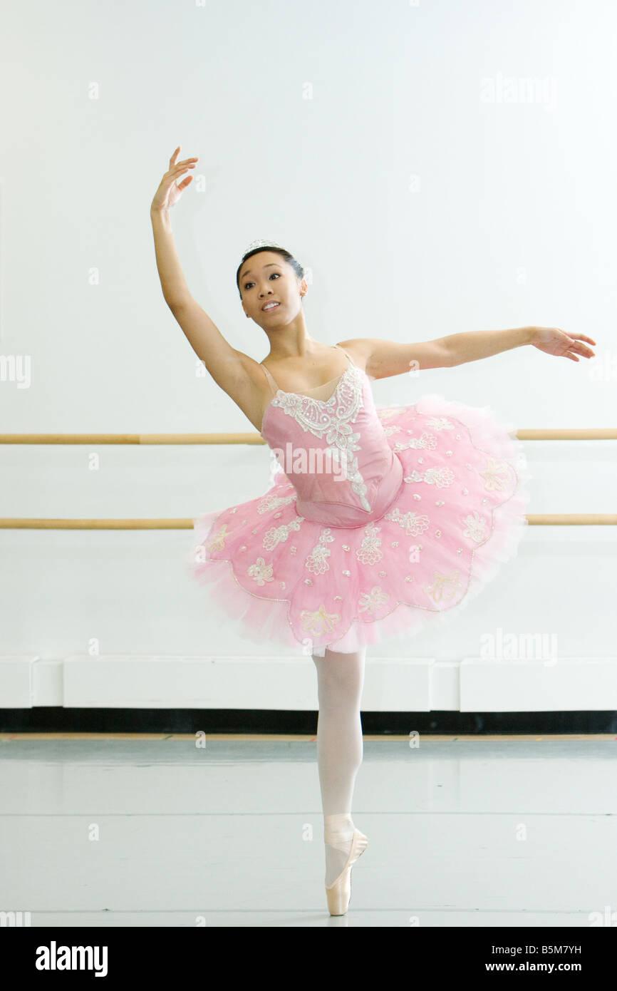 7f0eafc4c A ballerina in a pink tutu in an arabesque pose in a studio Stock ...