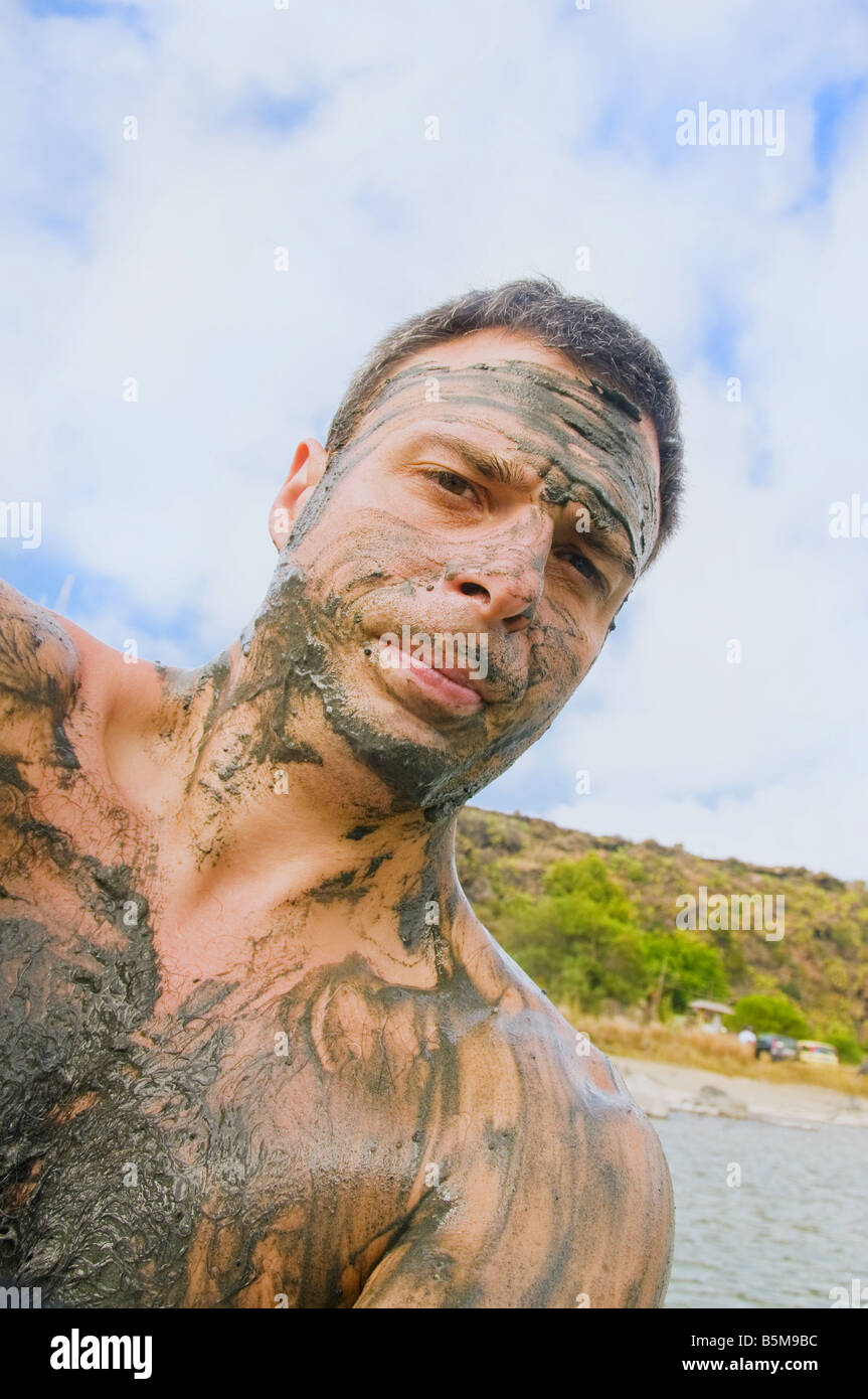 Portrait of man covered in mud standing in lake, Lago Specchio di Venere, island of Pantelleria, Sicily, Italy. Stock Photo