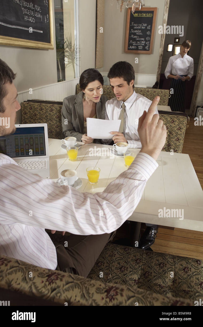 Soliciting the waitress while having a morning business meeting. - Stock Image