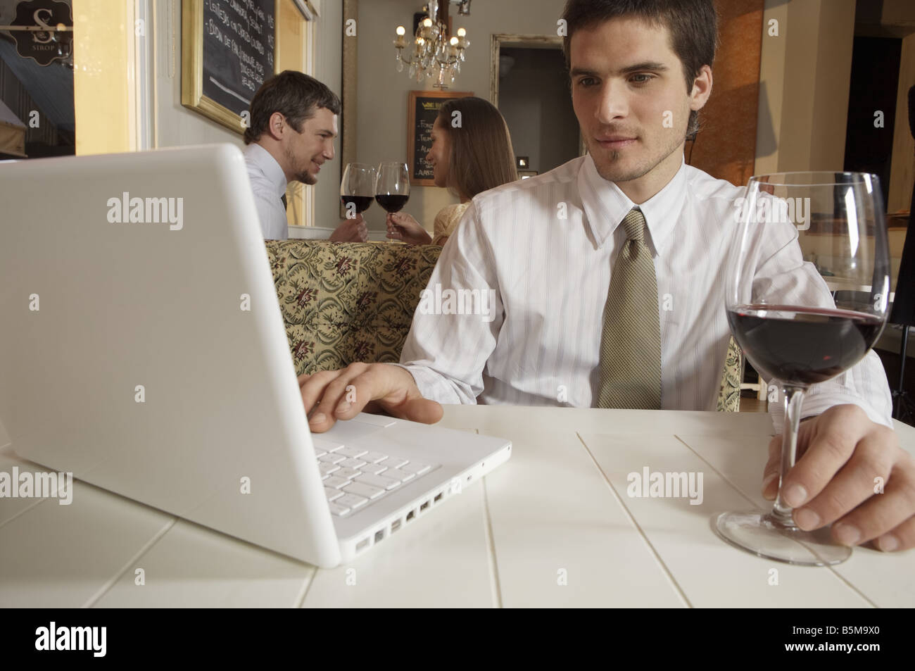 Man working with a laptop while holding a glass of wine. - Stock Image