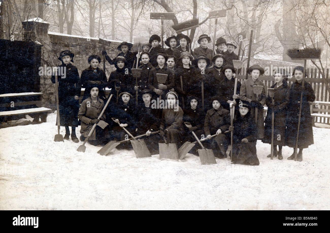 Group photo Girl school Snow Pedagogics School class Group photo of a girls class shovelling snow Photo Germany - Stock Image