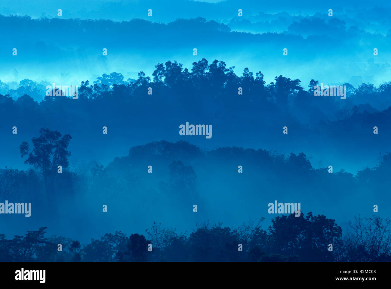 Misty morning of hilly area with ray of light Stock Photo