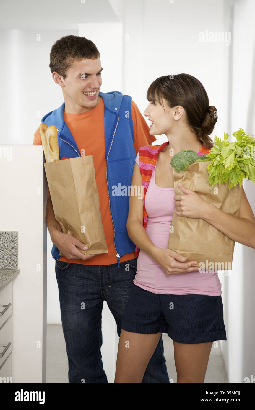 A teenage couple in a kitchen carrying groceries - Stock Image