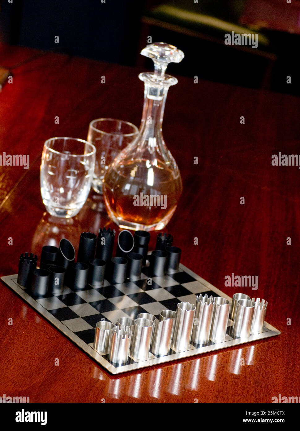 A decadent and modern style chess set with decanter and glasses - Stock Image