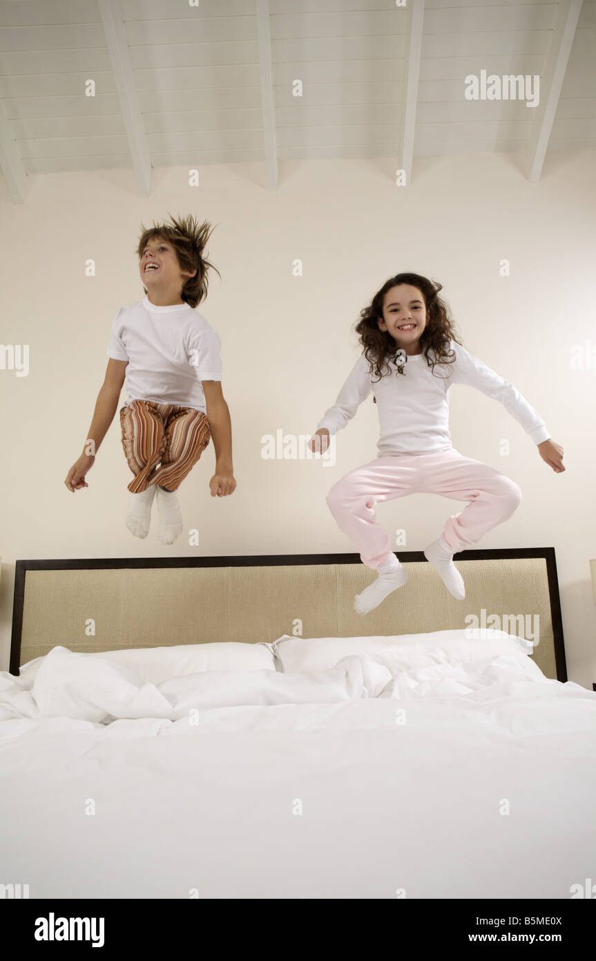 A boy and a girl jumping on a bed - Stock Image
