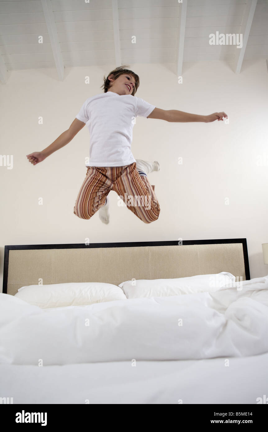 A little boy jumping on a bed - Stock Image