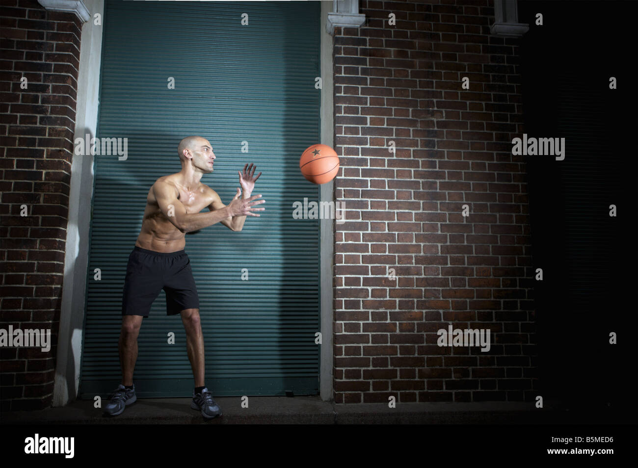 A shirtless man about to catch an airborne basketball - Stock Image