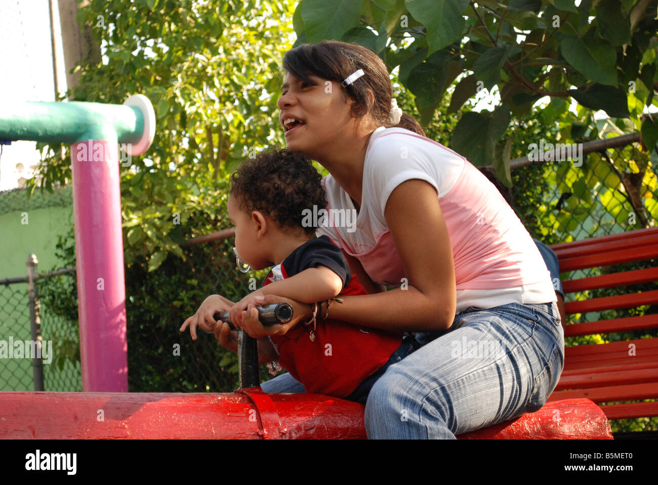 A teenager plays with a toddler in the seesaw at kids' area of a playground. - Stock Image
