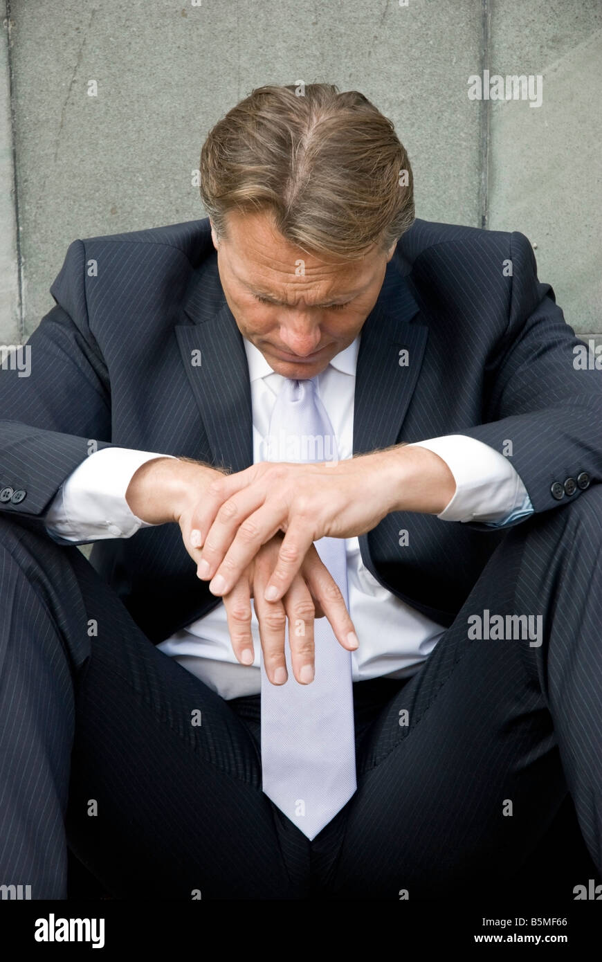 A sad stressed and dejected businessman sits on the floor alone outside his former workplace - Stock Image