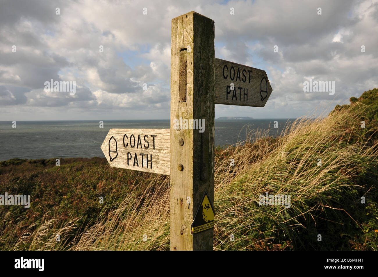A South West Coastal Path sign near Hartland Point in North Devon. In the distance Lundy Island is just visible. Stock Photo