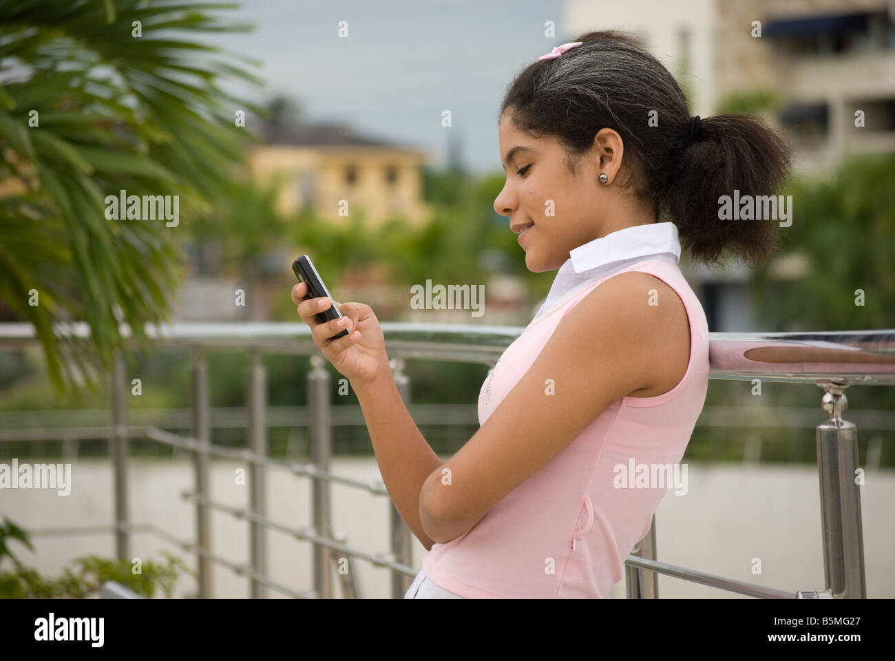 A young Latina teenager sends a text message/email by a mobile phone - Stock Image