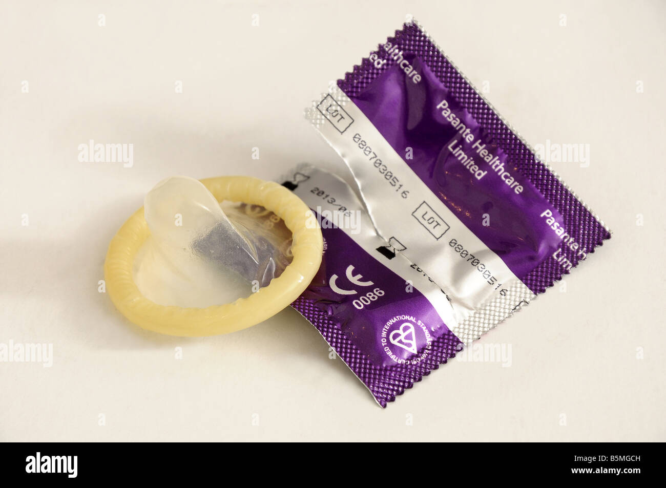Condom beside packaging - Stock Image
