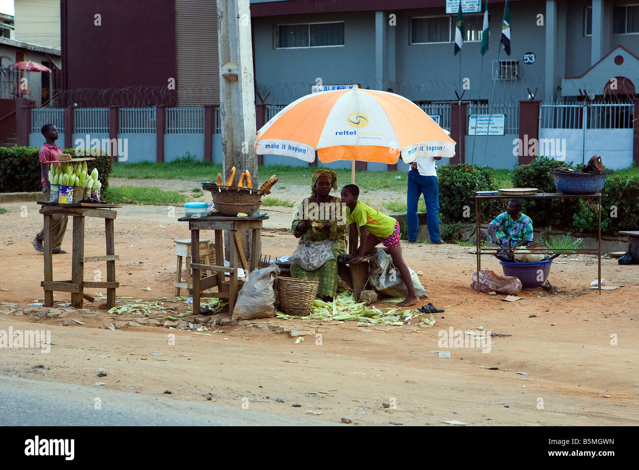 A roadside seller with her son sells hot and cold corn on the cob at the side of the road out of Lagos and near - Stock Image