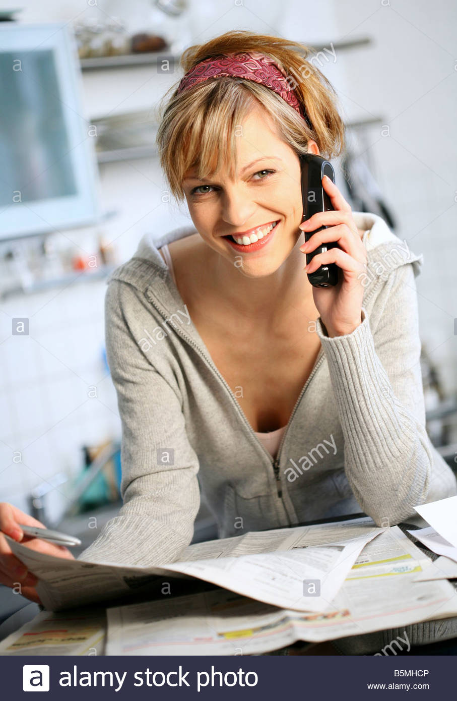 young woman searching for a job in a newspaper, making a phone call with mobile phone - Stock Image
