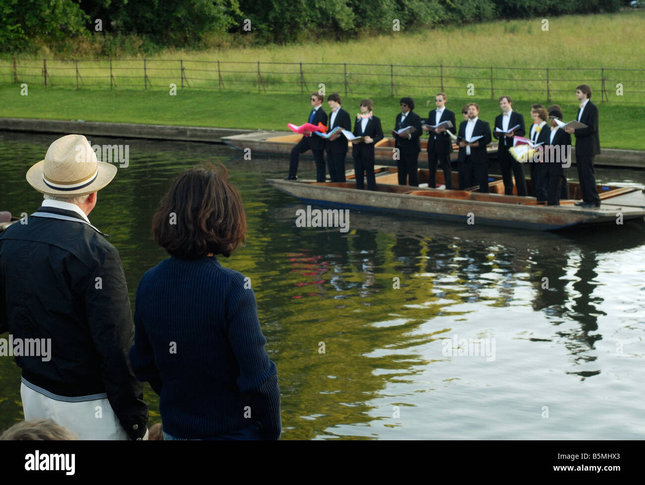 Couple admiring King's College Choral Scholars singing from punts on the River Cam, Cambridge - Stock Image