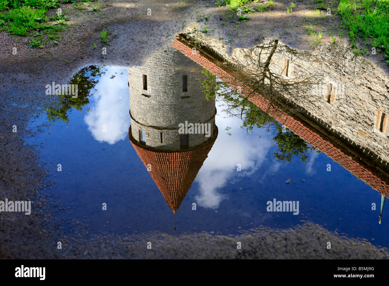 Reflection in a pool of water of medieval castle tower and rampart in Tallinn, Estonia - Stock Image