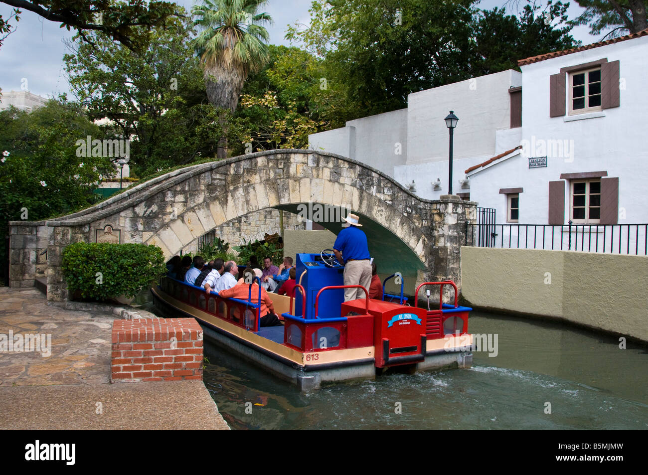 Boat plies the water River Walk, San Antonio River, downtown San Antonio, Texas. - Stock Image