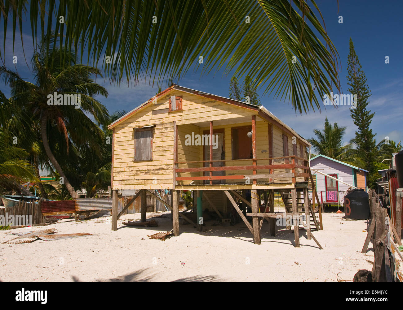 Delightful CAYE CAULKER BELIZE Wooden House On Stilts On Sand Beach With Palm Trees