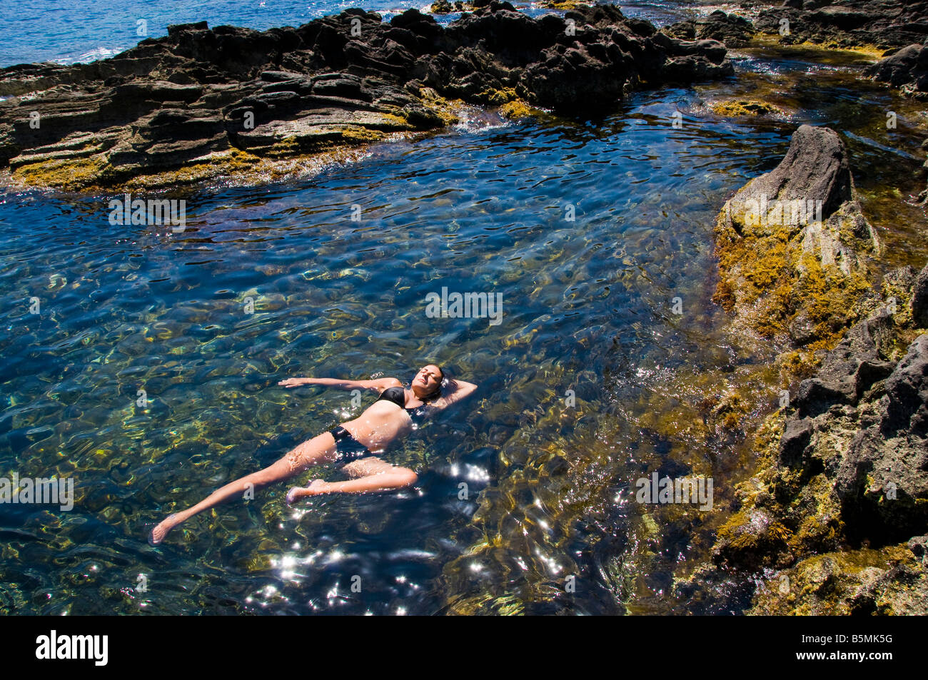 Woman floating in the Mediterranean water. Island of Pantelleria, Sicily, Italy. Stock Photo