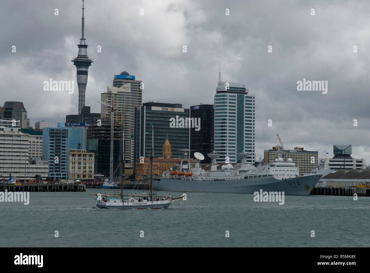 Small boat entering Auckland harbour with the city skyline in the background. - Stock Image
