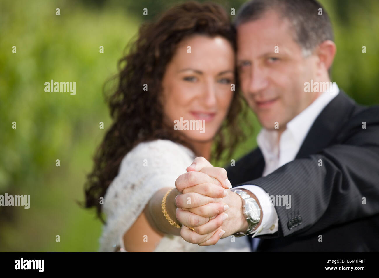 bride and groom hands joined, outdoor shot - Stock Image