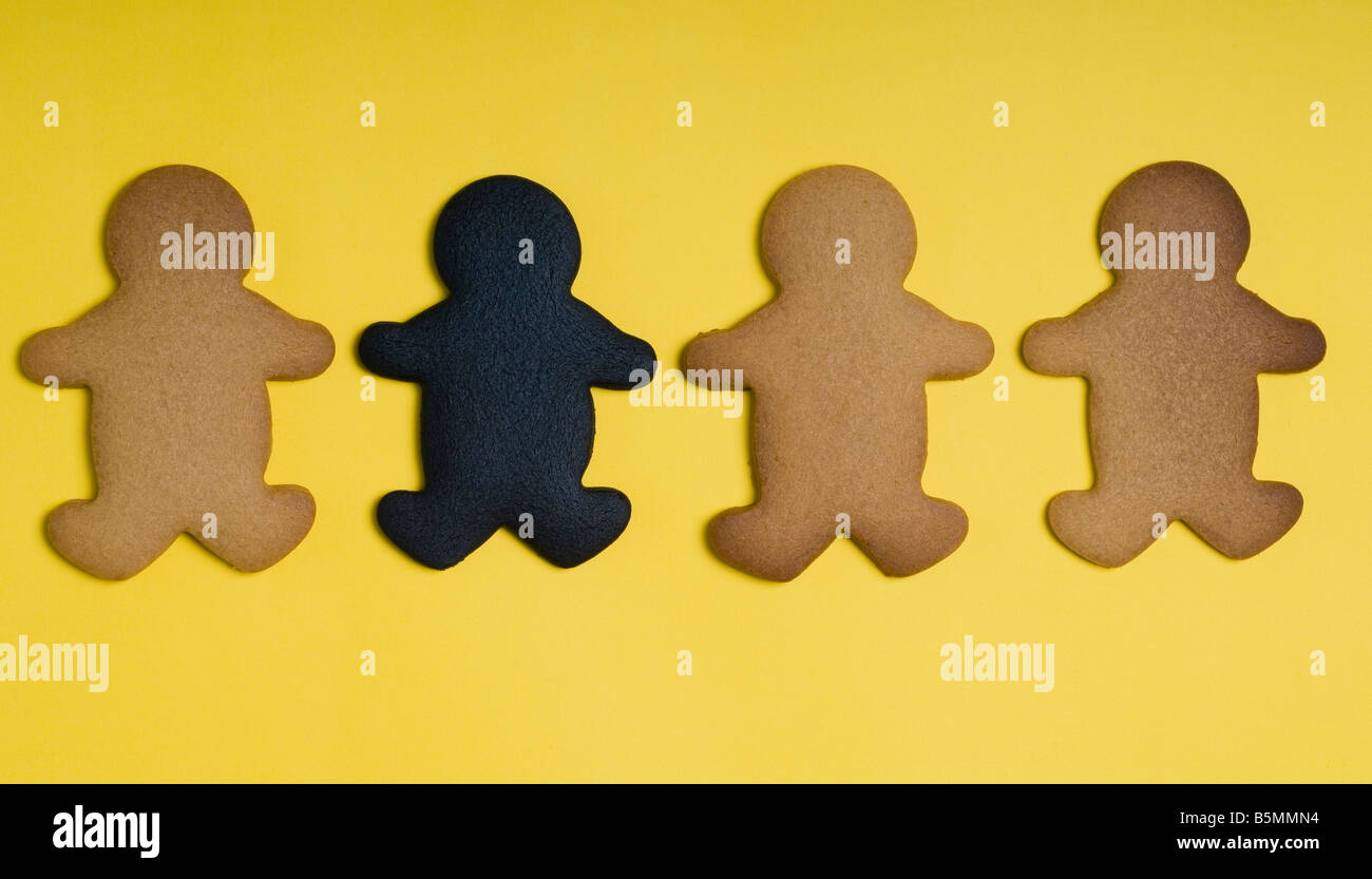 A burnt gingerbread cookie amongst several properly baked ones - Stock Image