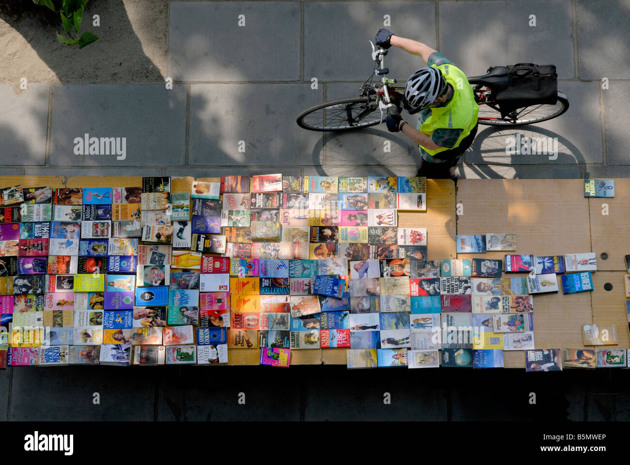 Man with bicycle looking at a table of books at the South Bank outdoor Book Market, London, England - Stock Image