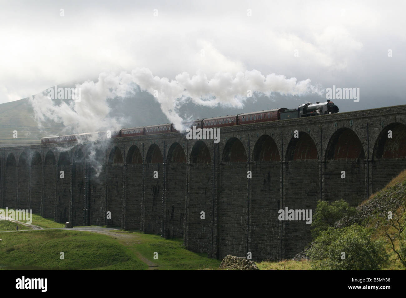 Steam locomotive pulling a passenger train over the Ribblehead viaduct on the mainline - Stock Image