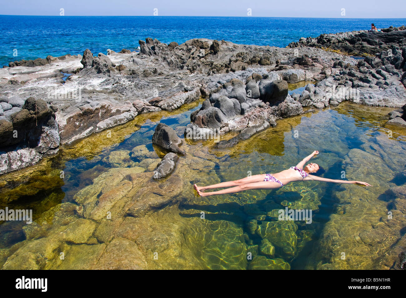 Woman floating in colorful water pool by the sea. Pantelleria Island, Sicily, Italy. - Stock Image