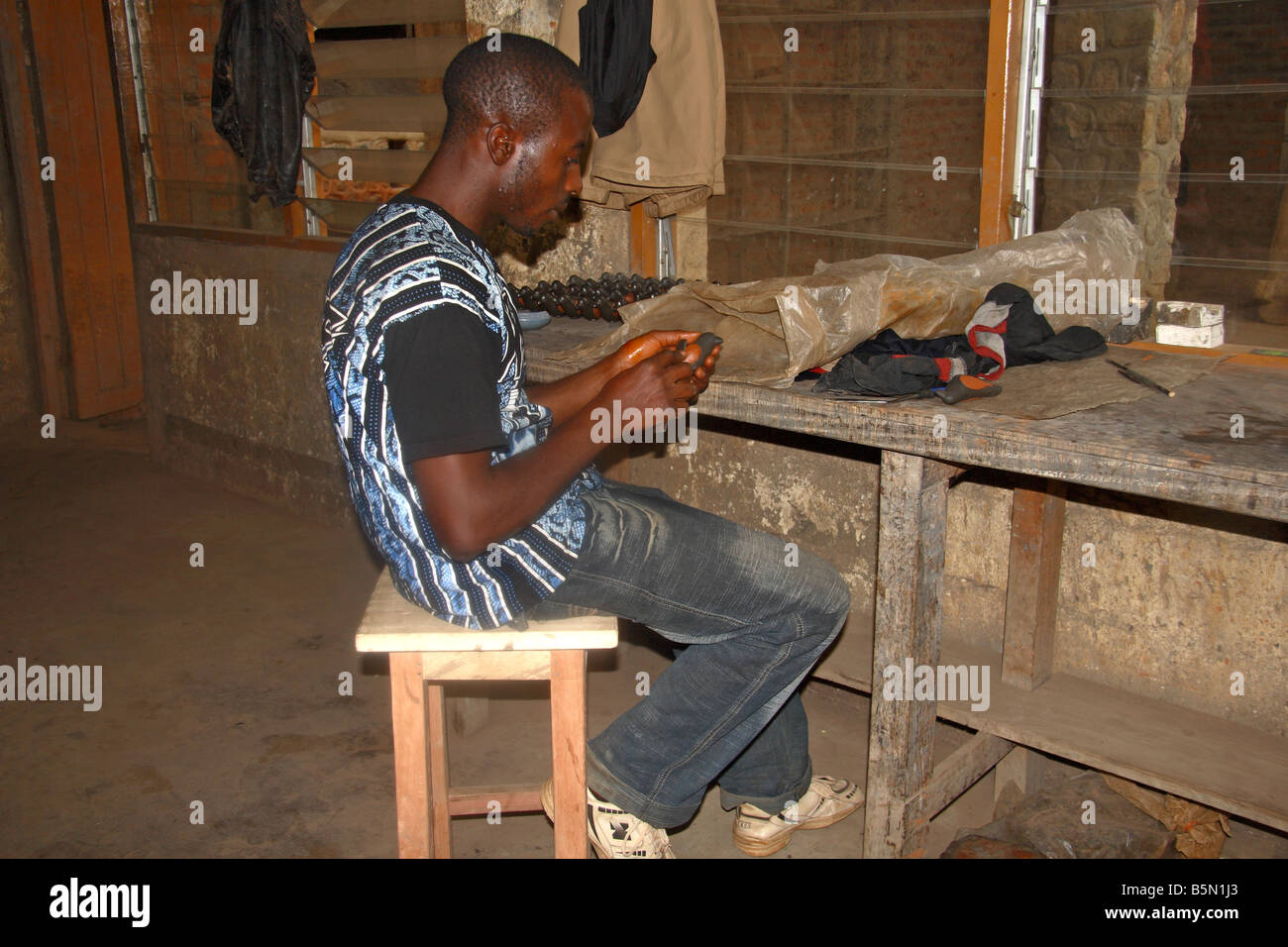 Pottery worker carving ceramic birds at Prespot pottery works Bamessing Northwest Province Cameroon - Stock Image