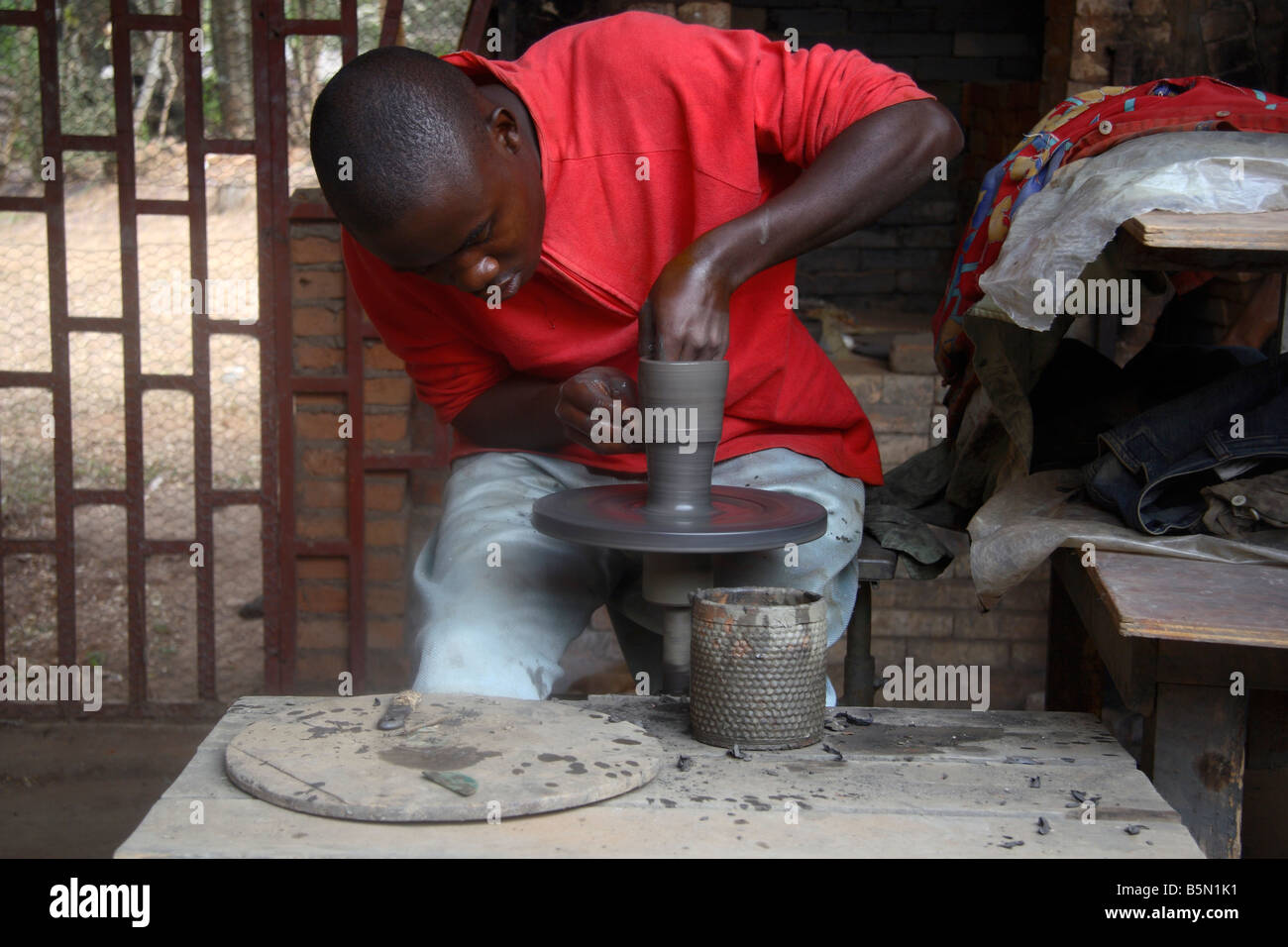 Pottery worker throwing pot at Prespot pottery works Bamessing Northwest Province Cameroon - Stock Image