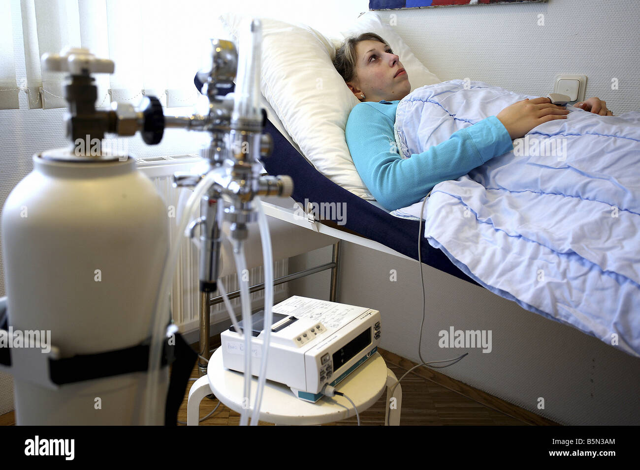 Patient lying in an anaesthetic recovery room after an operation - Stock Image
