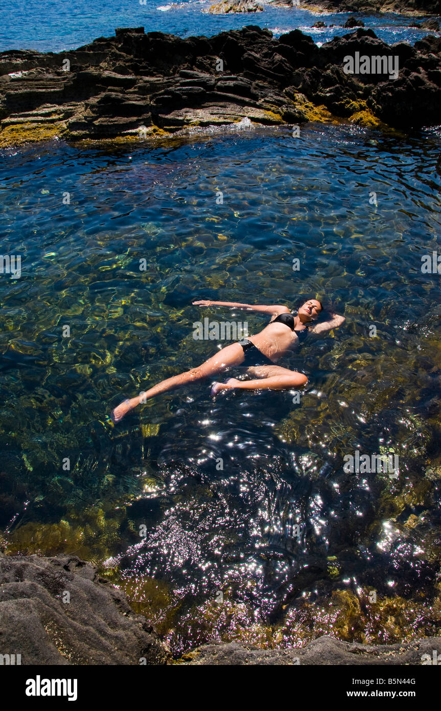 Woman floating in the Mediterranean water. Island of Pantelleria, Sicily, Italy. - Stock Image