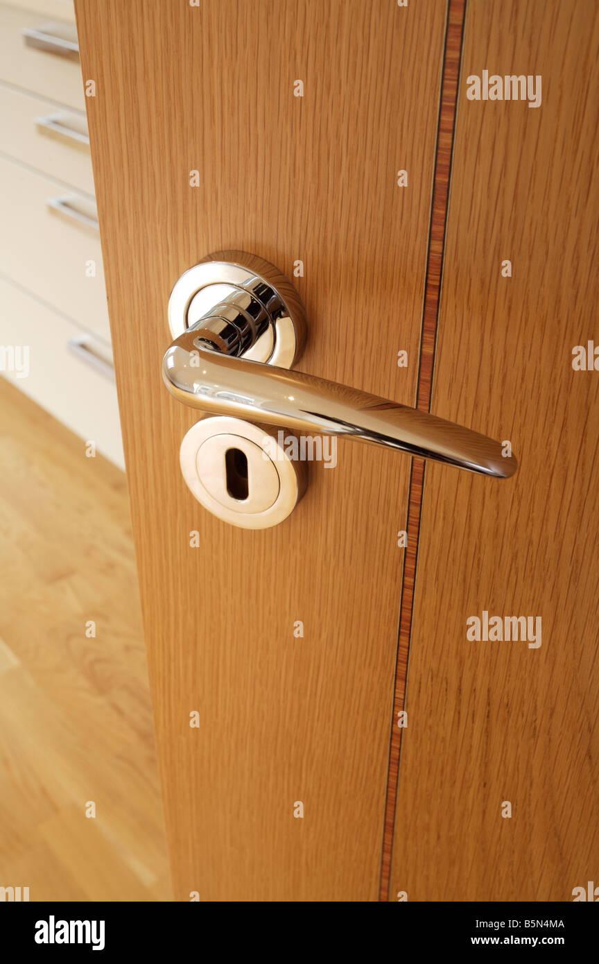 Chrome plated door handle and escutcheon on an inlaid oak veneered door in a luxury apartment & Chrome plated door handle and escutcheon on an inlaid oak veneered ...