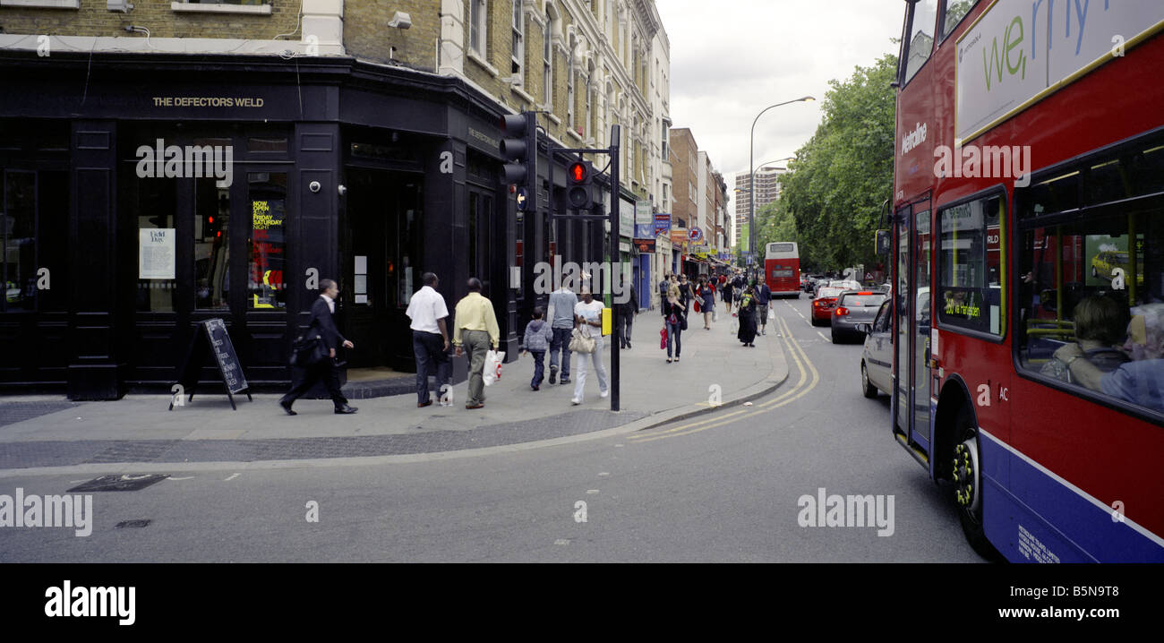A crossing and a red bus in London, in Shepherds Bush - Stock Image